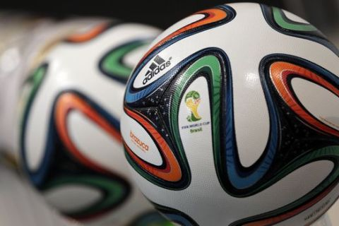 """FILE - In this May 8, 2014 file photo the adidas logo is printed on """"Brazuca"""", the official FIFA World Cup 2014 soccer ball, during the annual shareholders meeting in Fuerth, Germany. Sports equipment maker Adidas lowered its full-year profit target on Thursday, July 31, 2014, citing among other things increasing risk in the Russian market amid mounting political tensions over Ukraine. Adidas - a sponsor of the World Cup, which is to be held in Russia in 2018 - said it has decided to """"significantly reduce"""" its store opening plan in the region for this year and next, and to increase the number of store closures. (AP Photo/Matthias Schrader, File)"""