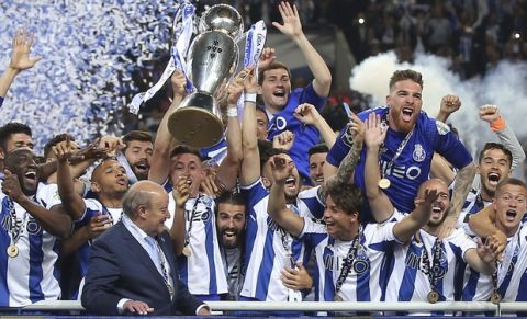Porto's team captain Hector Herrera lifts the Portuguese league champions trophy after the Portuguese league soccer match between FC Porto and Feirense at the Dragao stadium in Porto, Portugal, Sunday, May 6, 2018. Porto clinched the league title Saturday night, two rounds before the end, when Benfica and Sporting CP tied 0-0 in their Lisbon derby. (AP Photo/Luis Vieira)