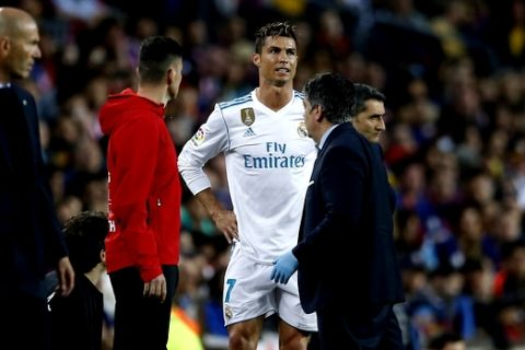 Real Madrid's Cristiano Ronaldo waits to come back on after treatment for an injury during a Spanish La Liga soccer match between Barcelona and Real Madrid, dubbed 'el clasico', at the Camp Nou stadium in Barcelona, Spain, Sunday, May 6, 2018. (AP Photo/Manu Fernandez)