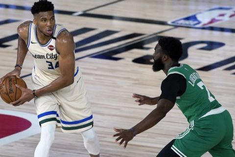 Milwaukee Bucks' Giannis Antetokounmpo (34) looks to pass around Boston Celtics' Jaylen Brown (7) during the first half of an NBA basketball game Friday, July 31, 2020, in Lake Buena Vista, Fla. (AP Photo/Ashley Landis, Pool)