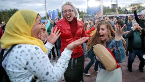 Fans celebrate Russia's fifth goal during the opening match of the 2018 soccer World Cup, between Russia and Saudi Arabia, in the fan zone in Yekaterinburg, Russia, Thursday, June 14, 2018. (AP Photo/Vadim Ghirda)