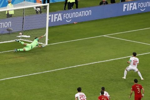 Iran's Karim Ansarifard scores on a penalty kick his side's opening goal during the group B match between Iran and Portugal at the 2018 soccer World Cup at the Mordovia Arena in Saransk, Russia, Monday, June 25, 2018. (AP Photo/Darko Bandic)