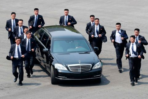 FILE - In this Friday, April 27, 2018, file photo, North Korean security persons run by a car carrying North Korean leader Kim Jong Un return to the North side for a lunch break after a morning meeting with South Korean President Moon Jae-in at the border village of Panmunjom in Demilitarized Zone. When Kim returned to the northern side of Panmunjom, a dozen bodyguards, all wearing black suits and blue ties, surrounded the vehicle and jogged beside it as it made its way to the North.(Korea Summit Press Pool via AP, File)