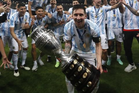 Argentina's Lionel Messi celebrates with the trophy after beating Brazil 1-0  in the Copa America final soccer match at the Maracana stadium in Rio de Janeiro, Brazil, Saturday, July 10, 2021. (AP Photo/Bruna Prado)