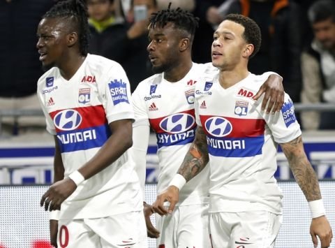 Lyon's Memphis Depay, right, celebrates with his teammates Maxwel Cornet, center, and Bertrand Traore, after he scored a goal against Toulouse during their French League One soccer match in Decines, near Lyon, central France, Sunday, April 1, 2018. (AP Photo/Laurent Cipriani)