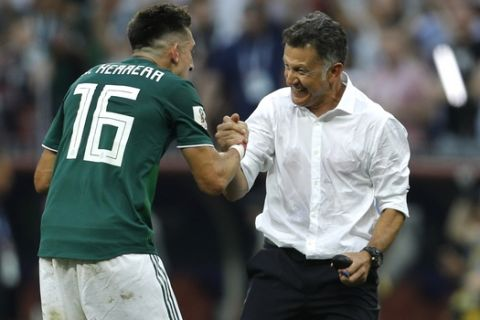 Mexico's Hector Herrera, left, celebrates with Mexico head coach Juan Carlos Osorio, at the end of the group F match between Germany and Mexico at the 2018 soccer World Cup in the Luzhniki Stadium in Moscow, Russia, Sunday, June 17, 2018. Mexico won 1-0. (AP Photo/Victor R. Caivano)