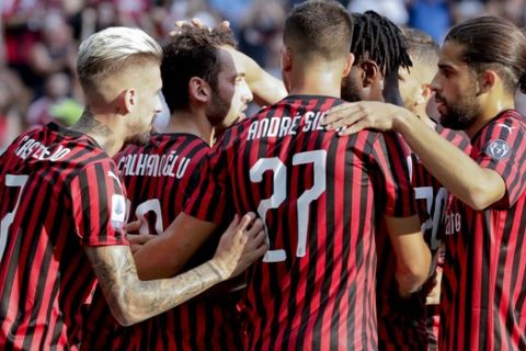 AC Milan's Hakan Calhanoglu, 2nd left, celebrates with teammates after scoring his side's opening goal during the Serie A soccer match between AC Milan and Brescia, at the San Siro stadium in Milan, Italy, Saturday, Aug. 31, 2019. (AP Photo/Luca Bruno)