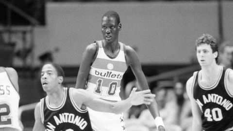 Washington Bullets' center Manute Bol towers over opponents and teammates alike, during game with the San Antonio Spurs in New York, Oct. 17, 1985.  (AP Photo/G. Paul Burnett)