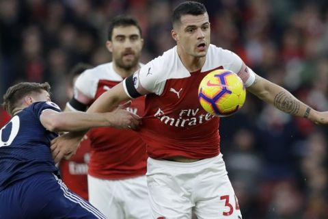 Arsenal's Granit Xhaka, right, challenges for the ball with Fulham's Tom Cairney during the English Premier League soccer match between Arsenal and Fulham at Emirates stadium in London, Tuesday, Jan. 1, 2019. (AP Photo/Kirsty Wigglesworth)