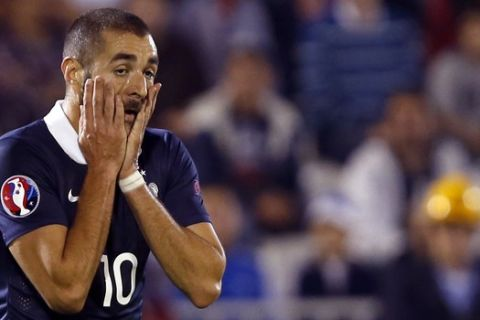FILE - In this  Sunday, Sept. 7, 2014 file photo, France's Karim Benzema reacts during his international friendly soccer match against Serbia, in Belgrade, Serbia. Karim Benzema has been indefinitely suspended from the French national team on Thursday, Dec. 10, over his involvement in an ongoing blackmail case, throwing a major doubt over his international career. The Real Madrid striker has been charged with conspiracy to blackmail, relating to an extortion scam over a sex tape featuring France teammate Mathieu Valbuena.  (AP Photo/Darko Vojinovic, file)