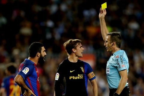 Referee Fernandez Borbalan, right, shows a yellow card to Atletico Madrid's Antoine Griezmann, center, during the Spanish La Liga soccer match between FC Barcelona and Atletico Madrid at the Camp Nou in Barcelona, Spain, Wednesday, Sept. 21, 2016. (AP Photo/Manu Fernandez)