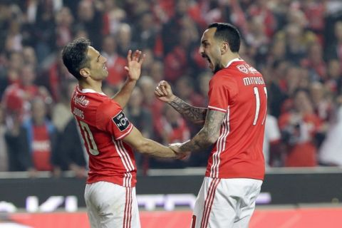 Benfica's Jonas, left, and Kostas Mitroglou celebrate after winning a penalty shot during a Portuguese league soccer match between Benfica and FC Porto at the Luz stadium in Lisbon, Saturday, April 1, 2017. (AP Photo/Armando Franca)