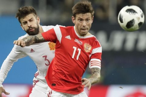 Russia's Fedor Smolov, right, struggles for the ball with Spain's Gerard Pique during the international friendly soccer match between Russia and Spain in St.Petersburg, Russia, Tuesday, Nov. 14, 2017. (AP Photo/Dmitri Lovetsky)
