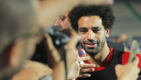 Egyptian national soccer team player and Liverpool's striker Mohammed Salah is surrounded by photographers and fans during Egypt's final training for the World Cup at Cairo Stadium in Cairo, Egypt, Saturday, June 9, 2018. (AP Photo/Amr Nabil)