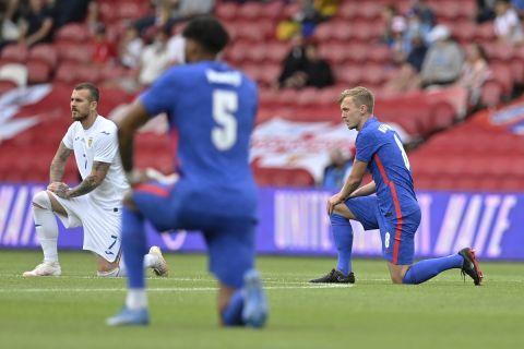 Οι παίκτες της Αγγλίας και της Ρουμανίας γονατίζουν πριν από την έναρξη του φιλικού αγώνα