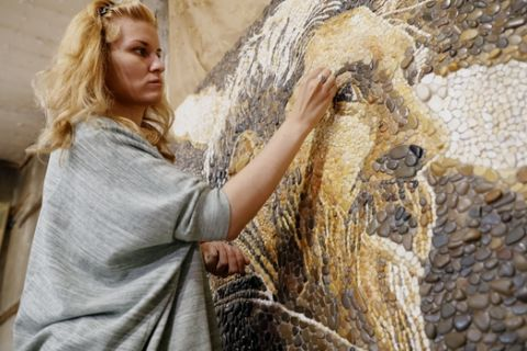 Anna Solnechnaya shows her creation of one of the pebble mosaics depicting Argentina's Lionel Messi ahead of the 2018 soccer World Cup at her workshop in Kazan, Russia, Wednesday, June 13, 2018. Kazan is one of World Cup match venues in Russia. (AP Photo/Eugene Hoshiko)