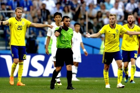 Swedish players ask referee Joel Aguilar from El Salvador to review a decision during the group F match between Sweden and South Korea at the 2018 soccer World Cup in the Nizhny Novgorod stadium in Nizhny Novgorod, Russia, Monday, June 18, 2018. the review resulted in a penalty for Sweden from which they scored the opening goal. (AP Photo/Petr David Josek)