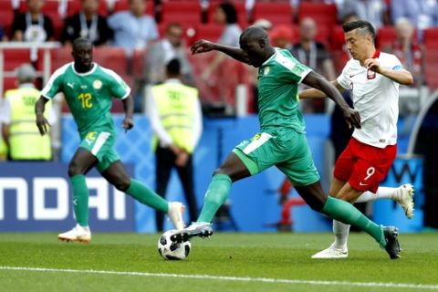 Senegal's Kalidou Koulibaly, center, and Poland's Robert Lewandowski compete for the ball during the group H match between Poland and Senegal at the 2018 soccer World Cup in the Spartak Stadium in Moscow, Russia, Tuesday, June 19, 2018. (AP Photo/Eduardo Verdugo)