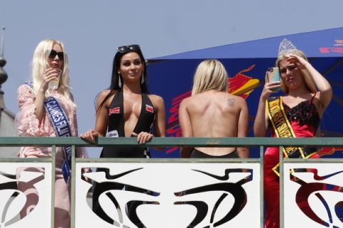 Women stand by the track watch the qualifying for Sunday's Monaco Formula One Grand Prix at the Monaco racetrack, in Monaco, Saturday, May 26, 2018. The Formula one race will be held on Sunday. (AP Photo/Claude Paris)