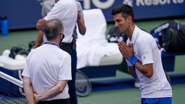 Novak Djokovic, of Serbia, talks with the umpire after inadvertently hitting a line judge with a ball after hitting it in reaction to losing a point against Pablo Carreno Busta, of Spain, during the fourth round of the US Open tennis championships, Sunday, Sept. 6, 2020, in New York. Djokovic defaulted the match. (AP Photo/Seth Wenig)