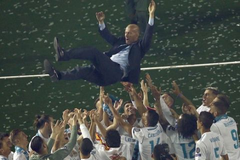 FILE - In this Sunday, May 27, 2018 file photo Real Madrid players lift head coach Zinedine Zidane into the air as they celebrate after winning the Champions League final, at the Santiago Bernabeu stadium in Madrid, Spain. (AP Photo/Francisco Seco, File)