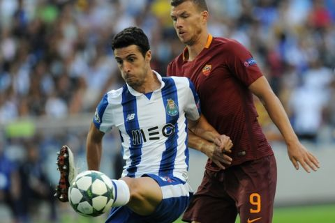 Porto's Ivan Marcano, left, controls the ball in front of Roma's Edin Dzeko during a Champions League play-offs first leg soccer match between FC Porto and AS Roma at the Dragao stadium in Porto, Portugal, Wednesday, Aug. 17, 2016. (AP Photo/Paulo Duarte)