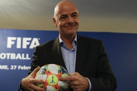 FIFA President Gianni Infantino holds the official ball of the upcoming Women's Soccer World Championship as he poses for photographers during a press conference at the end of an executive committee meeting in Rome, Wednesday, Feb. 27, 2019. (AP Photo/Gregorio Borgia)