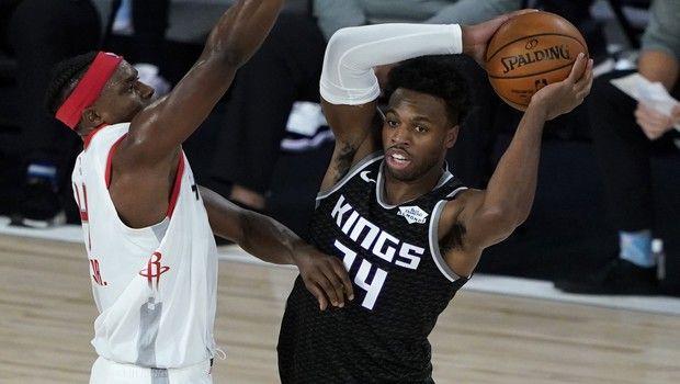 Sacramento Kings' Buddy Hield (24) passes around the defense of Houston Rockets' Danuel House Jr. (4), left, during the first half of an NBA basketball game Sunday, Aug. 9, 2020, in Lake Buena Vista, Fla. (AP Photo/Ashley Landis, Pool)