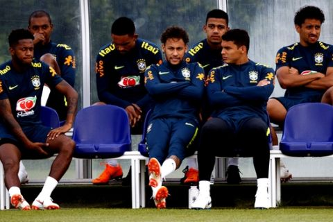 Brazil's Neymar sits next to captain Thiago Silva, right, and Fred, left, during the training session at Enfield Training Ground, in London, Tuesday June 5, 2018.   (John Walton/PA via AP)