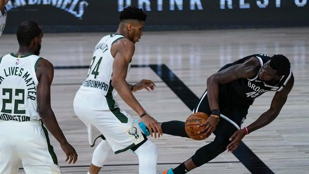 Brooklyn Nets forward Donta Hall, right, tries to save the ball in front of Milwaukee Bucks forward Giannis Antetokounmpo (34) during the first half of an NBA basketball game Tuesday, Aug. 4, 2020 in Lake Buena Vista, Fla. (AP Photo/Ashley Landis)