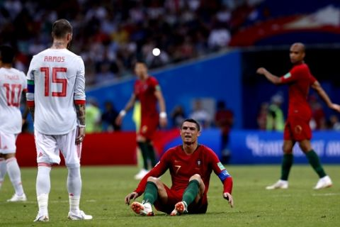 Portugal's Cristiano Ronaldo sits on the ground and look at Spain's Sergio Ramos as after the end of the the group B match between Portugal and Spain at the 2018 soccer World Cup in the Fisht Stadium in Sochi, Russia, Friday, June 15, 2018. (AP Photo/Manu Fernandez)