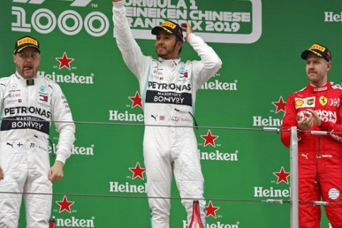 Mercedes driver Lewis Hamilton of Britain, center, waves next to his teammate Valtteri Bottas of Finland, left, and Ferrari driver Sebastian Vettel of Germany, right, after winning the Chinese Formula One Grand Prix at the Shanghai International Circuit in Shanghai, Sunday, April 14, 2019. Bottas finished second as Vettel was third. (AP Photo/Andy Wong)