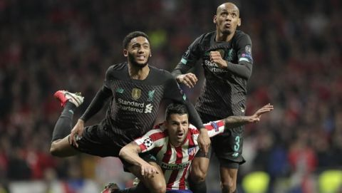 Liverpool's Fabinho, right, and Joe Gomez jump for a header with Atletico Madrid's Vitolo during a first leg, round of 16, Champions League soccer match between Atletico Madrid and Liverpool at the Wanda Metropolitano stadium in Madrid, Spain, Tuesday Feb. 18, 2020. (AP Photo/Bernat Armangue)