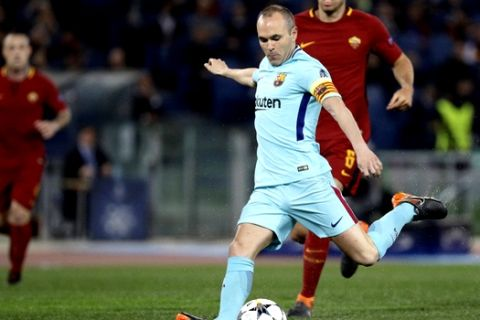 Roma's Kevin Strootman, rear, runs after Barcelona's Andres Iniesta as he takes a shot on goal during the Champions League quarterfinal second leg soccer match between between Roma and FC Barcelona, at Rome's Olympic Stadium, Tuesday, April 10, 2018. (AP Photo/Gregorio Borgia)
