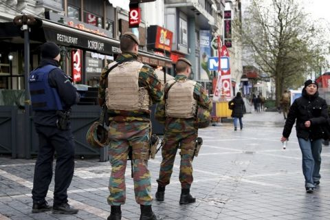 A Belgian police officer and soldiers patrol in a shopping area after security was tightened following the fatal attacks in Paris, in Brussels, Belgium, November 21, 2015. REUTERS/Francois Lenoir