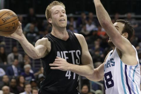 Brooklyn Nets' Justin Hamilton (41) passes around Charlotte Hornets' Miles Plumlee (18) in the first half of an NBA basketball game in Charlotte, N.C., Tuesday, Feb. 7, 2017. (AP Photo/Chuck Burton)
