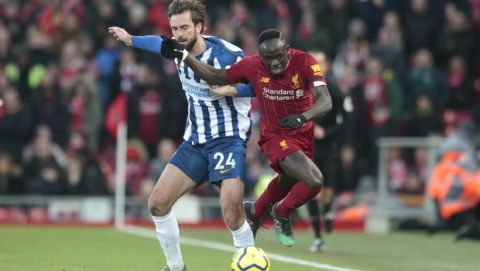 Liverpool's Sadio Mane, right, fights for the ball against Brighton's Davy Proepper during the English Premier League soccer match between Liverpool and Brighton at Anfield Stadium, Liverpool, England, Saturday, Nov. 30, 2019. (AP Photo/Jon Super)