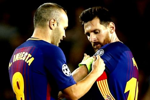 Barcelona's Andres Iniesta hands over the captain's armband to Lionel Messi during a Champions League group D soccer match between FC Barcelona and Juventus at the Camp Nou stadium in Barcelona, Spain, Tuesday, Sept. 12, 2017. (AP Photo/Francisco Seco)
