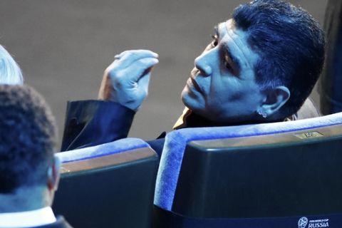 Argentine soccer legend Diego Maradona gestures after taking his seat before the 2018 soccer World Cup draw in the Kremlin in Moscow, Friday Dec. 1, 2017. (AP Photo/Pavel Golovkin)