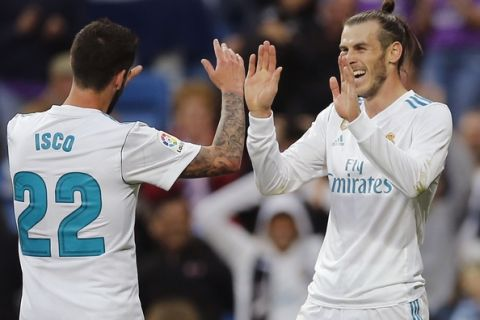 Real Madrid's Gareth Bale, right, celebrates with Isco after scoring his side's 2nd goal during a Spanish La Liga soccer match between Real Madrid and Celta at the Santiago Bernabeu stadium in Madrid, Spain, Saturday, May 12, 2018. (AP Photo/Paul White)