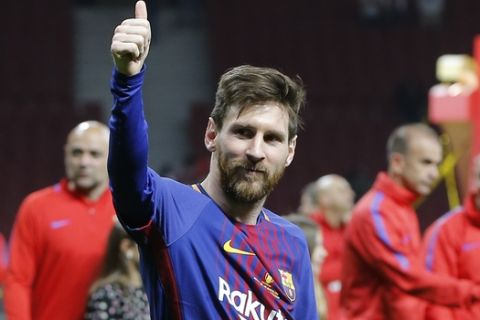 Barcelona's Lionel Messi celebrates during an award ceremony after defeating Sevilla 5-0 in the Copa del Rey final soccer match at the Wanda Metropolitano stadium in Madrid, Spain, Saturday, April 21, 2018. (AP Photo/Paul White)