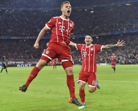 Bayern's Joshua Kimmich, left, celebrates his side's opening goal with team mate James during the semifinal first leg soccer match between FC Bayern Munich and Real Madrid at the Allianz Arena stadium in Munich, Germany, Wednesday, April 25, 2018. (AP Photo/Kerstin Joensson)