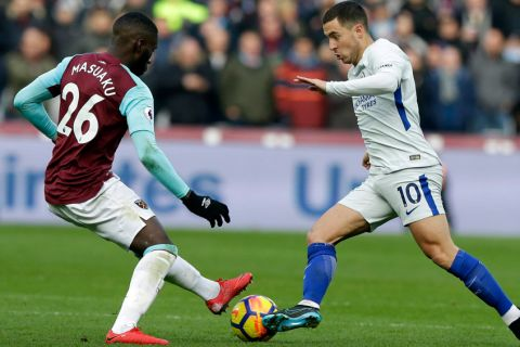 Chelsea's Eden Hazard, right, is challenged by West Ham United's Arthur Masuaku during the English Premier League soccer match between West Ham United and Chelsea at the London stadium in London, Saturday, Dec. 9, 2017. (AP Photo/Alastair Grant)