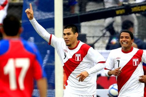 Peru's Hernan Rengifo, center, celebrates his goal as teammate Reimond Manco runs behind during a friendly match with Costa Rica in Lima, Peru, Friday Oct. 8, 2010. (AP Photo/Martin Mejia)