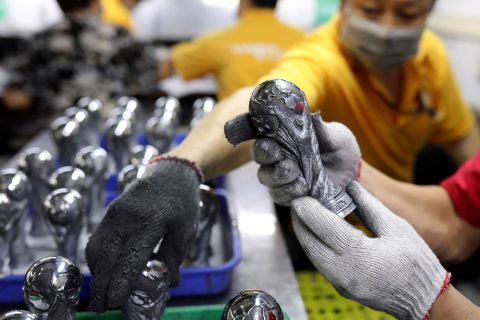 In this June 11, 2018, photo, Chinese worker check on the miniature FIFA World Cup trophies at a factory in Dongguan in south China's Guangdong province. The 21st World Cup begins on Thursday, June 14, 2018, when host Russia takes on Saudi Arabia. (Color China Photo via AP)