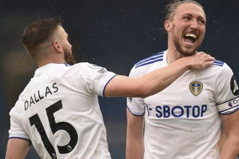 Leeds United's Stuart Dallas, left, is congratulated by teammate Luke Ayling after scoring his team's first goal during the English Premier League soccer match between Leeds United and Tottenham Hotspur at Elland Road in Leeds, England, Saturday, May 8, 2021. (AP Photo/Oli Scarff/Pool)