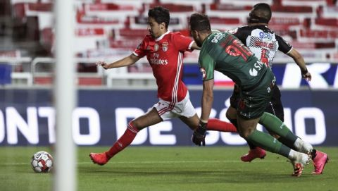 Benfica's Andre Almeida, left, scores the opening goal during the Portuguese League soccer match between Benfica and Boavista at the Luz stadium in Lisbon, Portugal, Saturday, July 4, 2020. The Portuguese League soccer matches are being played without spectators because of the coronavirus pandemic. (Manuel de Almeida/Pool via AP)