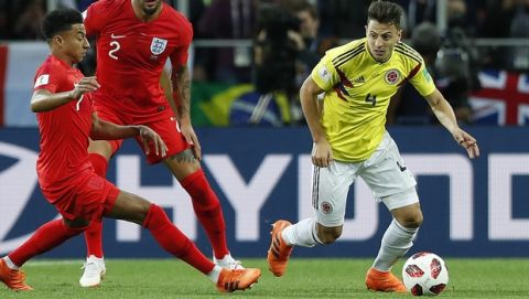 Colombia's Santiago Arias, right, and England's Jesse Lingard challenge for the ball during the round of 16 match between Colombia and England at the 2018 soccer World Cup in the Spartak Stadium, in Moscow, Russia, Tuesday, July 3, 2018. (AP Photo/Alastair Grant)