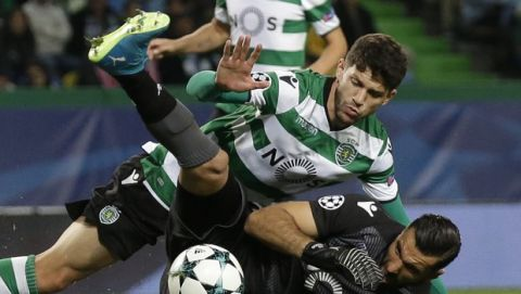 Sporting's Tobias Figueiredo, top, collides with Olympiakos goalkeeper Lefteris Houtesiotis during a Champions League, Group D soccer match between Sporting CP and Olympiakos at the Alvalade stadium in Lisbon, Wednesday Nov. 22, 2017. (AP Photo/Armando Franca)