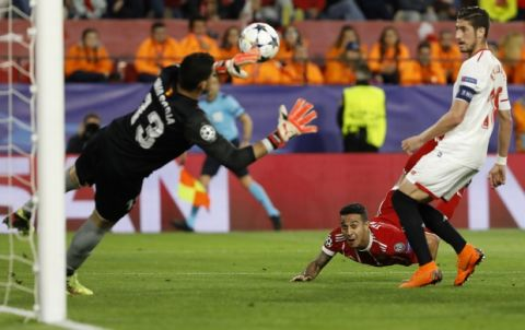 Bayern's Thiago, background, scores his side's second goal during the Champions League quarter final first leg soccer match between Sevilla FC and FC Bayern Munich at the Sanchez Pizjuan stadium in Seville, Spain, Tuesday, April 3, 2018. (AP Photo/Miguel Morenatti)